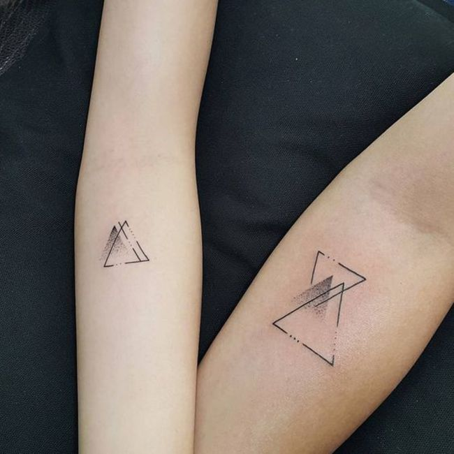 Matching geometric blackwork tattoos.