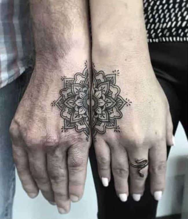 Matching mandala tattoos on the hands.